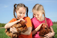 Two girls holding chickens