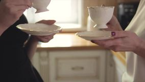 Two girls holding cups of tea. 1 stock footage