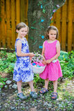 Two Girls Holding an Easter Basket in a Garden Royalty Free Stock Images