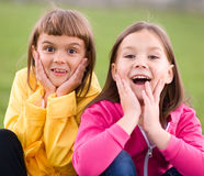 Two girls holding face in disbelief. Two cute girls holding face in disbelief Royalty Free Stock Photos