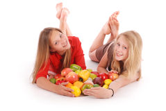 Two girls holding fresh fruits Stock Photos
