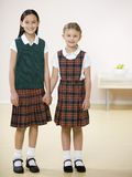 Two girls holding hands. Two young girls holding hands in uniform Stock Image