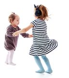 Two girls holding hands sisters dance in a circle Royalty Free Stock Image