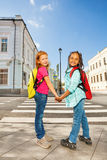 Two girls holding hands and standing near road Royalty Free Stock Photography