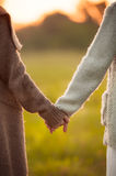 Two girls holding hands together stock photos