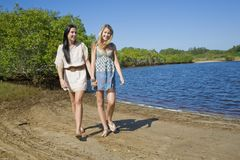 Two girls holding hands walkin by the creek Stock Image