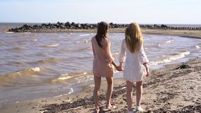 Two girls holding hands walking along the coastline, smiling and laughing. Video from backside stock video footage
