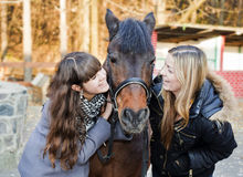 Two girls holding a horse Royalty Free Stock Photos