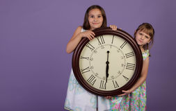 Two girls holding a large wall clock Stock Image