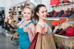 Two girls holding a paper shopping bags in the boutique. Two smiling cheerful young girls holding a paper shopping bags in the boutique Royalty Free Stock Photo