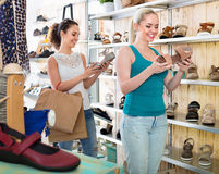 Two girls holding a paper shopping bags in the boutique Royalty Free Stock Photography