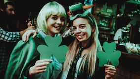 Two Girls Holding A Shamrocks. St Patrick`s Day. Celebrating Concept. Bar Counter. Good Festive Mood. Bright Lights. Club Visitors. Having Fun. Resting royalty free stock image