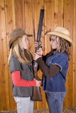 Two girls holding shotgun looking at each other Royalty Free Stock Photos