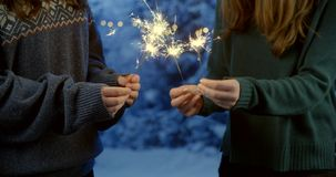 Two Girls Holding Sparkling Firework in the Hands. In winter night stock video
