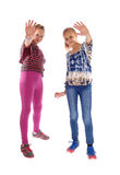 Two girls holding there hands up. Royalty Free Stock Images