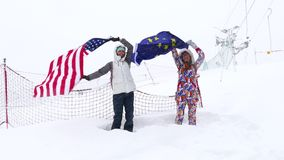Two girls holds Flags of EU and USA waving in the wind. Two girls holds Flags of EU and USA waving in the wind outdoors on ski slope stock footage