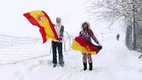 Spanish Flag waving in the wind. Two girls holds German and Spanish Flag waving in the wind outdoors on ski slope stock video footage