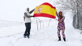 Spanish Flag waving in the wind. Two girls holds Spanish Flag waving in the wind outdoors on ski slope stock footage