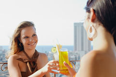 Two girls on holidays in Cuba. Young caucasian female couple drinking cocktails and smiling on terrace in Havana, Cuba. Horizontal shape, waist up, copy space Stock Photography
