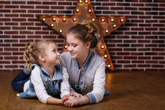 Two girls at home infront brick wall and decorative star Royalty Free Stock Photography