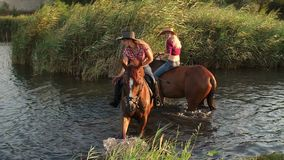 Two girls with the horses swimming in the lake. Two horses swimming in the lake, hit a hoof in the water creating splashes, slow motion stock footage