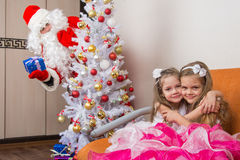 Two girls hug on couch, santa claus peeping from behind trees Stock Photography