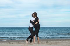 Two girls hugging on the beach royalty free stock image