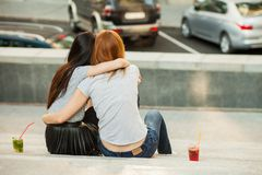 Two girls hugging and drink cold cocktails. Two girls hugging and drink cocktails, pretty friends, nice girlfriends walk around the city and drink lemonade. back Royalty Free Stock Photo
