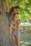 Two girls hugging each other in forest Stock Photography