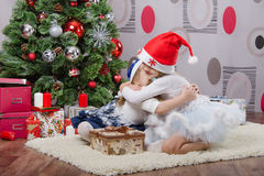 Two girls hugging near a Christmas tree Stock Image
