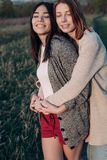 Two girls hugging outdoors Stock Photos