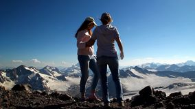 Two  girls hugging in the top of the mountain with his arms raised above his head stock footage