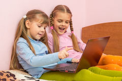 Two girls include laptop at work, sitting on bed Stock Photos