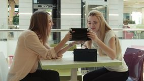 Two girls in intertainment center speaks and look in the tablet. Two beautiful girls look in the touchpad in shopping entertainment center stock video