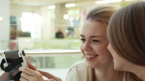 Two girls in intertainment center speaks and look in the tablet stock video