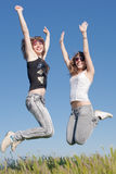 Two girls in jeans jumping outdoors Stock Photos