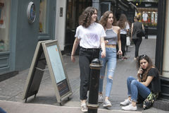 Two girls in jeans pass by a girl sitting on the sidewalk Royalty Free Stock Photo