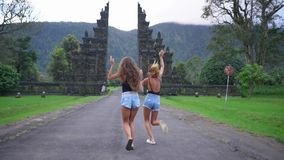Two girls in jeans shorts enjoy their time in exotic place, running and smiling. Two long-legged girls in jeans shorts enjoy their time in exotic place, running stock video