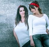 Girls in jeans and a white T-shirt. Two girls in jeans and a white T-shirt, against the wall background, the concept of urban clothing, female friendship and royalty free stock photos