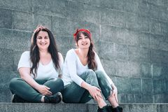 Girls in jeans and a white T-shirt. Two girls in jeans and a white T-shirt, against the wall background, the concept of urban clothing, female friendship and stock photos