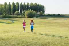 Two girls jogging. In nature Royalty Free Stock Images
