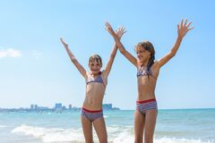 Free Two Girls Joyfully Raised Their Hands Up On The Sea On Vacation And Swimming Royalty Free Stock Photography - 190212647