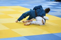 Girls compete in Judo. Two Girls judoka in kimono compete on the tatami Royalty Free Stock Photography