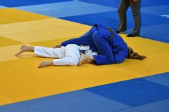 Girls compete in Judo. Two girls judoka in kimono compete on the tatami Royalty Free Stock Image