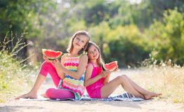 Two girls and a juicy red watermelon. Royalty Free Stock Image