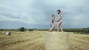 Two girls jump on haystack. Young happy children jump on a hay bale in the field in the summer day,blue sky.Summer vacation stock footage