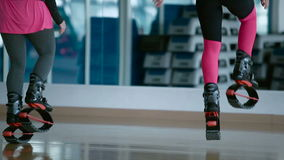 Two girls jump in the kangoo shoes in front of the mirror stock video footage