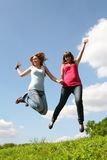 Two girls jump under blue sky. Two jumping girls on green herb under blue sky in park Royalty Free Stock Photos