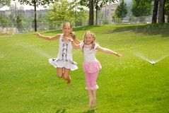 Two girls jump up barefoot in park under splash Royalty Free Stock Images