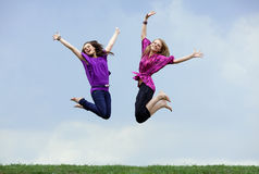 Two girls jumping Stock Images
